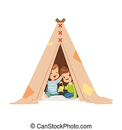 Cute little boys sitting in a tepee tent with a burning...