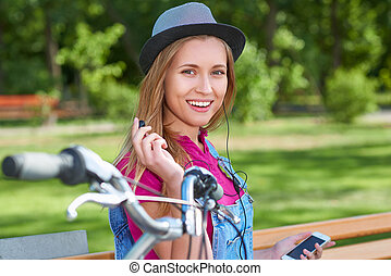Young woman listening to music on her smart phone resting at...