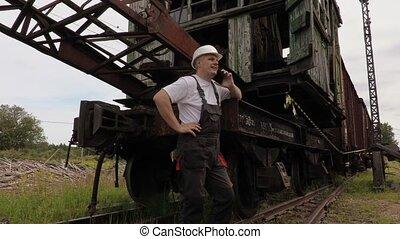 Railway employee talking on phone near the old railway machinery