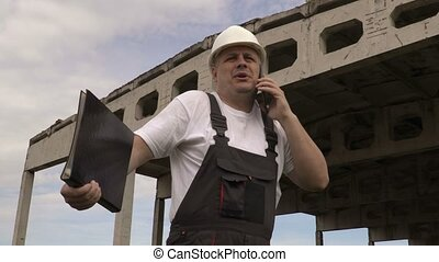 Engineer talking on smart phone near unfinished building