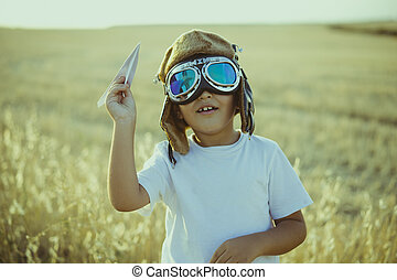 Imagination, Boy playing to be airplane pilot, funny guy with aviator cap and glasses, carries in his hand a plane made of paper