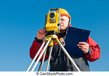Surveyor worker making measurement in a field with...