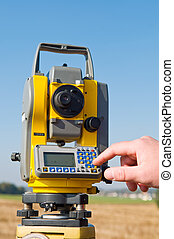 survey equipment theodolite - closeup human hand making data...