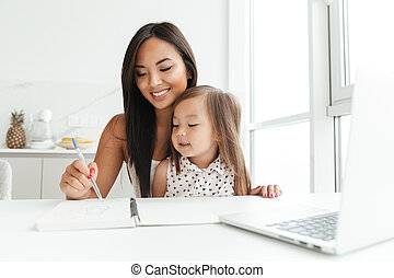 Mom with little cute asian girl using laptop writing notes -...