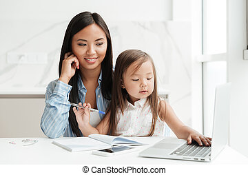 Mom with little daughter using laptop computer - Image of...
