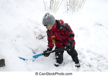 Boy shovels snow. - A little boy helps out by shoveling snow...