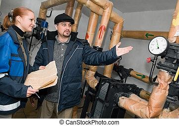 heating engineers in boiler room - Two engineers inspecting...