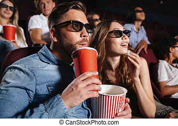 Concentrated loving couple friends sitting in cinema -...