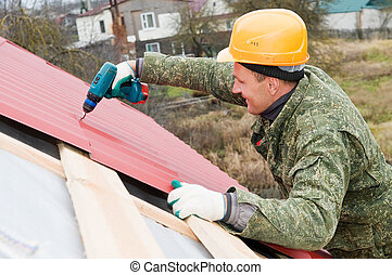 roofing works with screwdriver - builder worker at roofing...