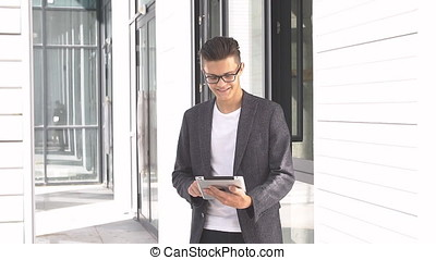 Young businessman uses tablet on background of modern...