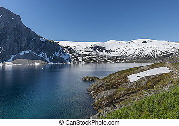 fjord with snow in summer in norway - The famous road in...