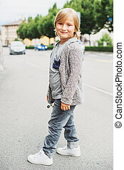 Outdoor vertical portrait of funny little 6 year old kid...