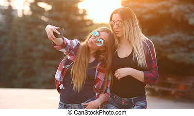 Portrait of a happy two smiling girls making selfie photo on...
