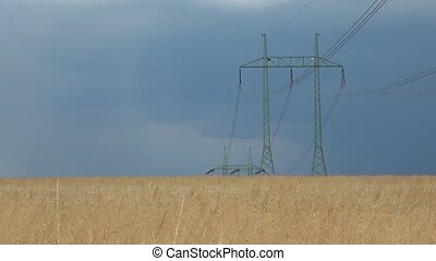 High voltage lines and power pylons in a flat and green...