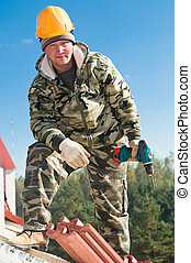 tiler roofer with screwdriver - Carpenter in hardhat with...