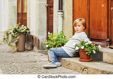 Outdoor portrait of cute 5-6 year old little boy, wearing...