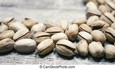 Pistachios on wooden background with copyspace in studio....
