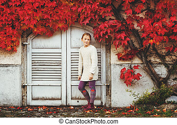 Autumn portrait of pretty little girl wearing knitted beige pullover dress, posing against wall with red ivy leaves