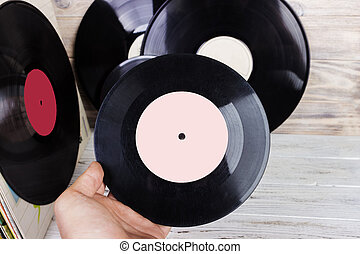 collection of old vinyl record lp's with sleeves on a wooden background. Browsing through vinyl records collection. Music background. Copy space.