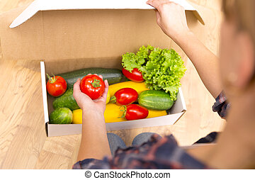 Box of fresh organic vegetables and fruits delivered to home - online grocery shopping service concept