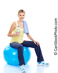 Fitness and gym Smiling young woman with water Isolated over...