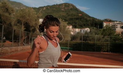 Professional sportswoman jumping on tennis court listening...