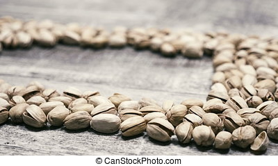 Delicious Pistachios on wooden background with copyspace in...