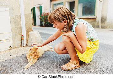 Cute little girl playing with furry ginger cat outside....
