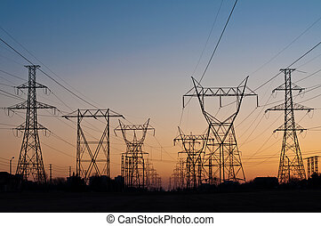 Electrical Transmission Towers Electricity Pylons at Sunset...