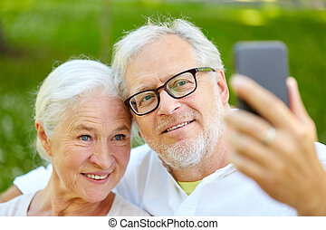 senior couple with smartphone taking selfie in summer -...