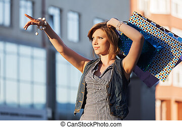 Happy young fashion woman with shopping bags on a city...
