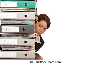 Frustrated business woman looks behind behind a folder stack...