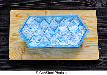 A blue plastic ice cube tray with frost on it on a cutting...