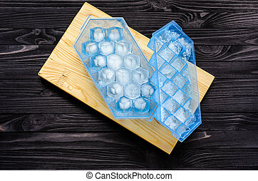 A blue plastic ice cube tray with ice cubes - A blue plastic...