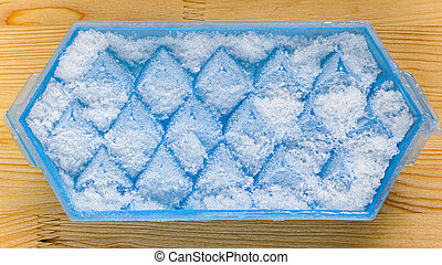 A blue plastic ice cube tray with frost on it on a kitchen...