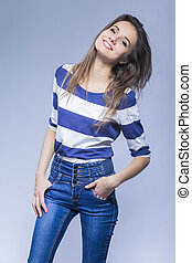 Youth Lifestyle  Concepts. Natural Portrait of Smiling Sensual Brunette Girl with Long Hair Posing in Trendy Jeans and Striped Shirt Against White