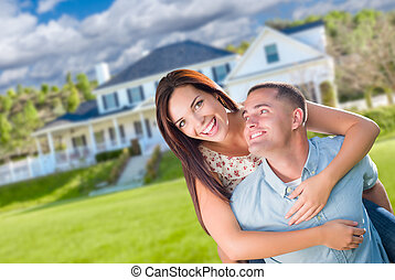 Playful Young Military Couple Outside A Beautiful New Home.