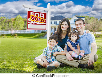 Young Family With Children In Front of Custom Home and Sold For Sale Real Estate Sign.