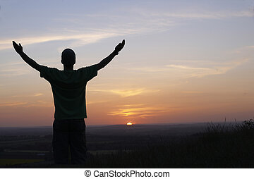 Man and sunset - man with arms outstretched in front of...