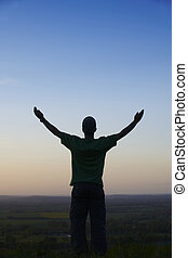 Man standing with arms outstretched in front of landscape at...