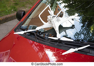 Damaged white drone on broken car windshield