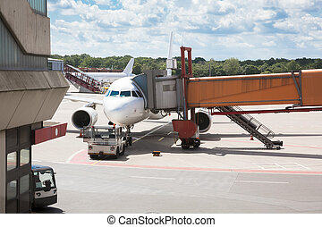 Passenger boarding bridge attached to airplane