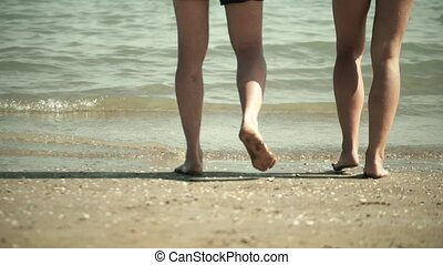 Legs of a couple walking into the sea