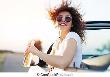 Young woman drinking a beer and looking the sunset. She is sitting in a sportive car.