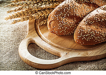 Wooden carving board bread wheat ears on sacking background.