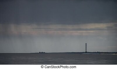 Stormy clouds mover over water with lighthouse - Stormy...