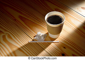 Paper cup of coffee in the morning light on wooden background