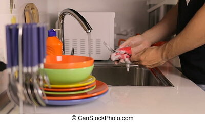 The process of washing dishes in the sink - The process of...