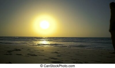 Young couple is holding hands and walking to sunset on the golden sandy beach. Two hipster in love, walks, dreams, relaxes at amazing beautiful sunset. Ocean waves washes feet of beautiful couple