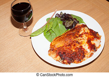 Lasagna pasta meal with salad and red wine. Classic lasagne Italian food.